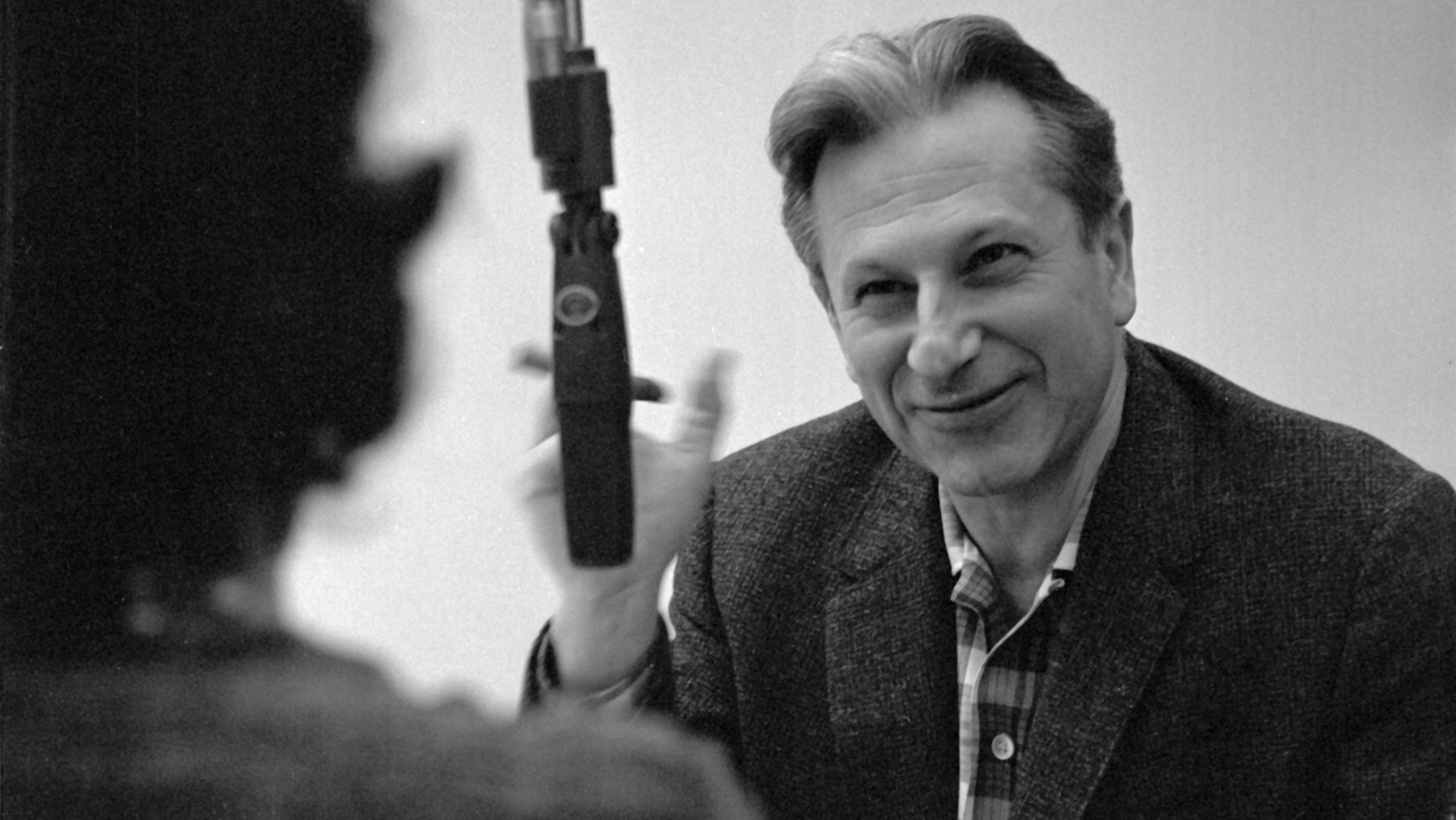 Black and white photograph of a young Studs Terkel in the radio studio.