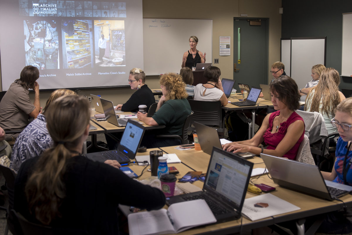 Photograph of a woman speaking to students in a computer lab.