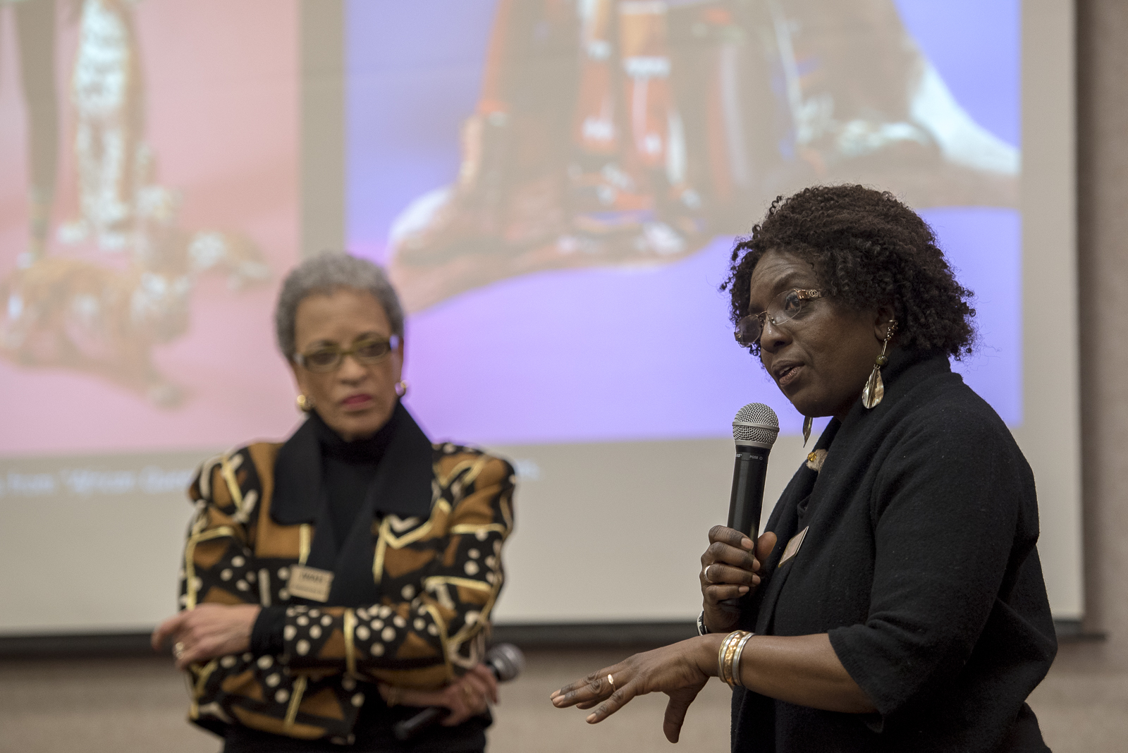 Two african american women speaking at a conference.