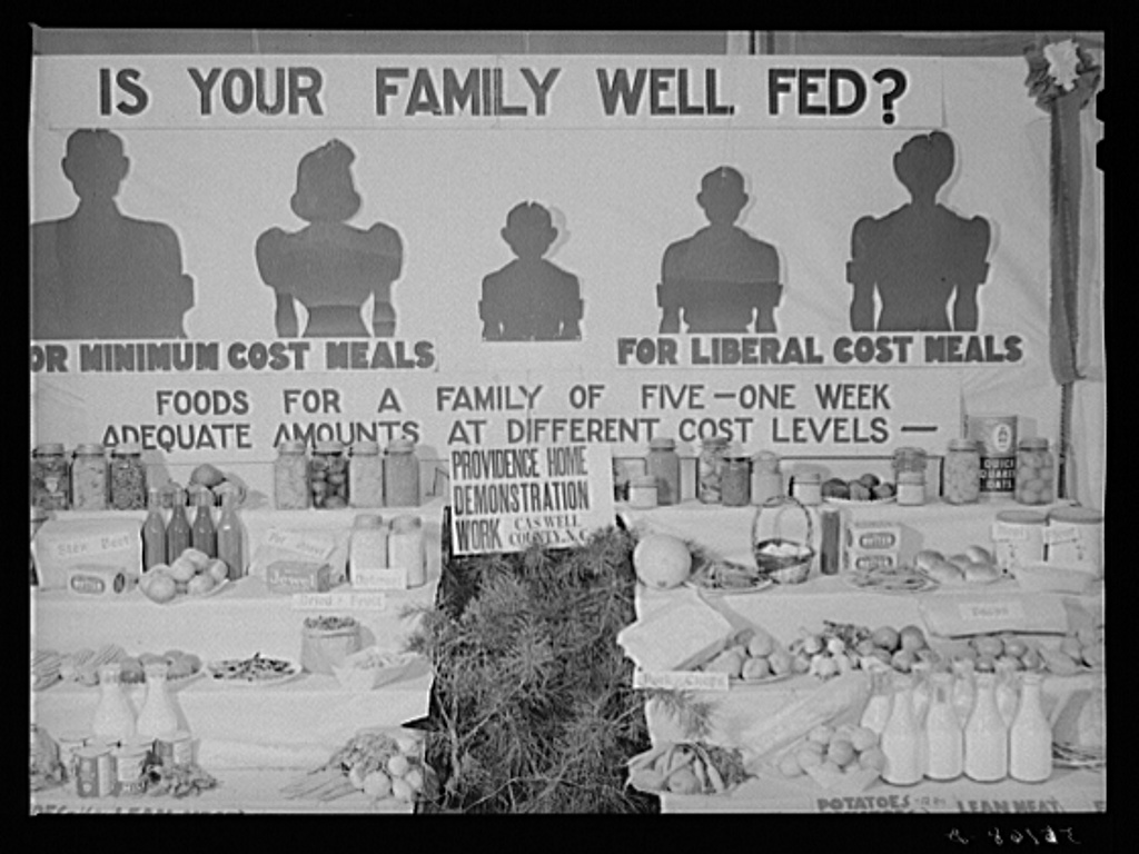 Black and white photo of fairground booth showing food needed to feed a family.
