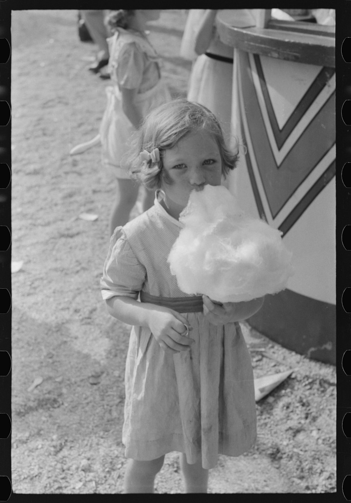 Black and white photo of a girl eating cotton candy