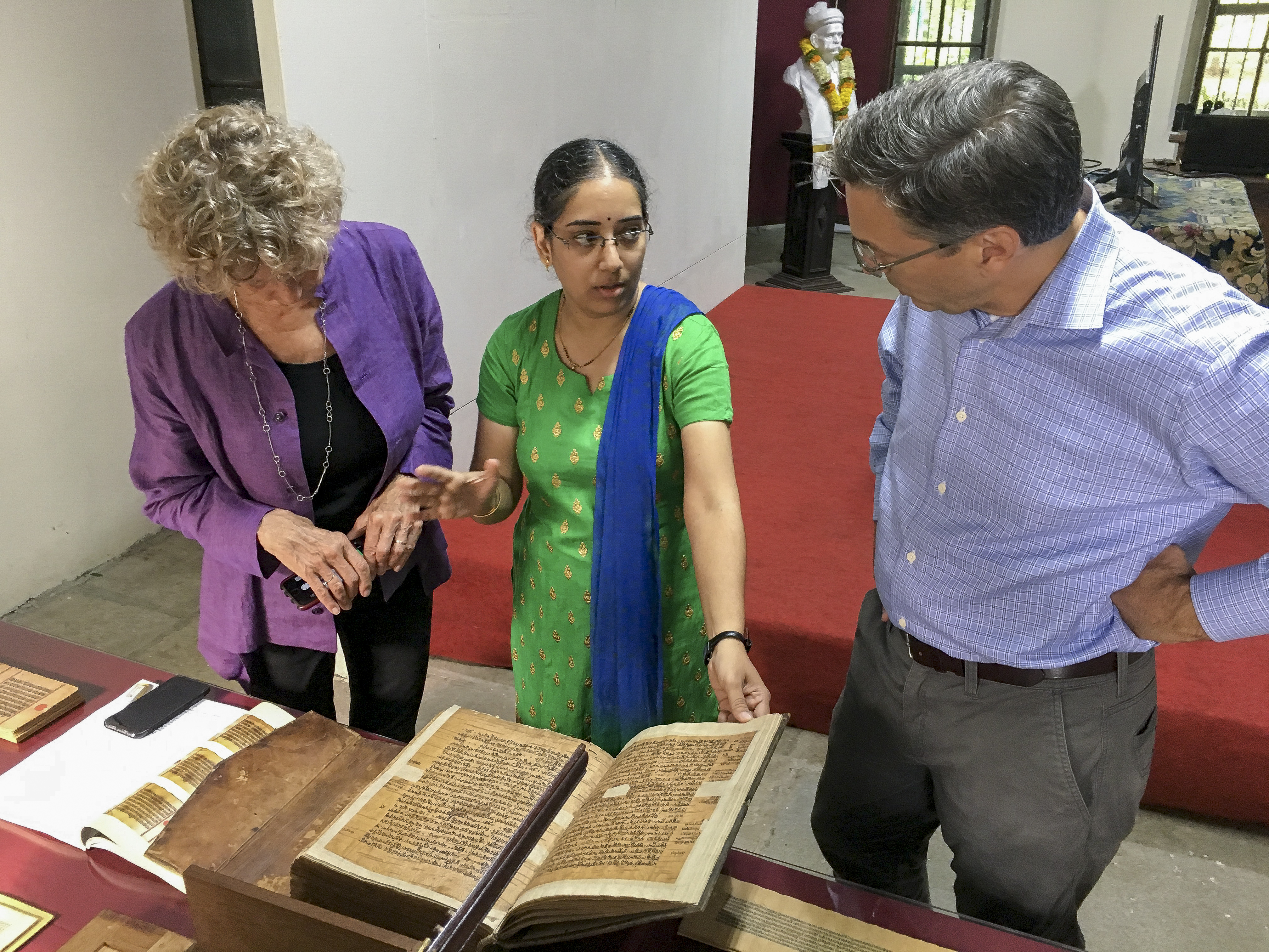 photograph of 3 people looking at an ancient book